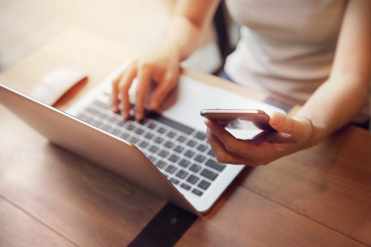 Femme utilisant son téléphone devant son ordinateur